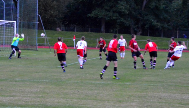 Alain Kinney (far right) lashes home a late equaliser